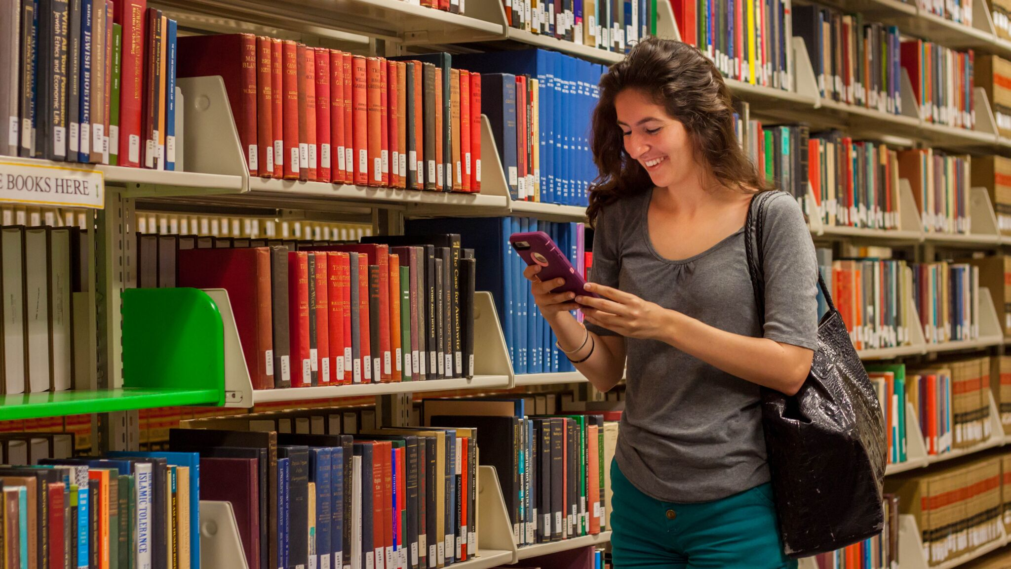Student checking phone in library